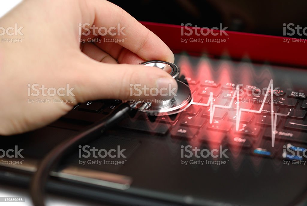An ECG signal on a laptop with a stethoscope held on royalty-free stock photo