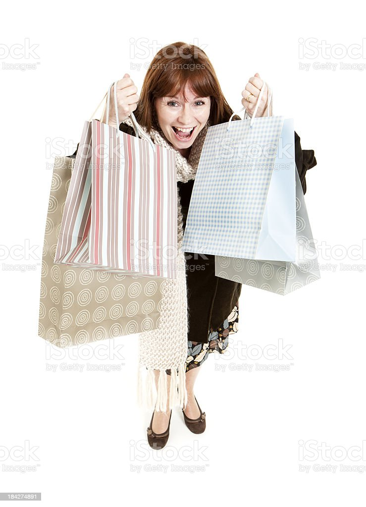 An ecstatic woman holding shopping bags in the air. stock photo