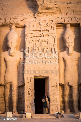 Abu Simbel, Egypt - November 14, 2018 :   the guardian of the Nefertari's temple of Hathor keeps watch at the entrance of the temple and takes advantage of this moment of tranquility to watch his cell phone