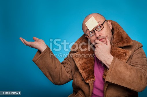 istock An elderly bald man in a fur coat has a blank post it on the forehead,  on the blue background. 1130058571