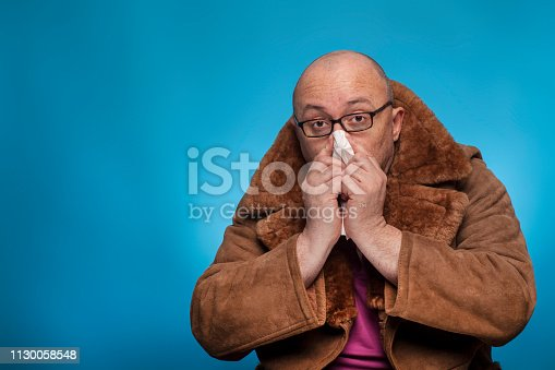 istock An elderly bald man in a fur coat is snuff his handkerchief,  on the blue background. 1130058548