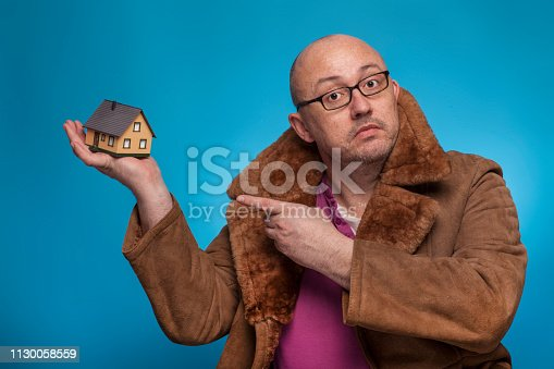 istock An elderly bald man in a fur coat points his finger at a house,  on the blue background. 1130058559
