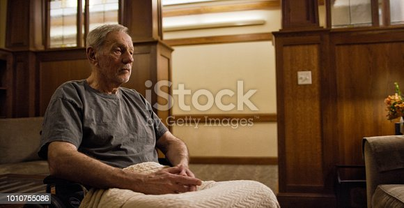 istock An Elderly Caucasian with a Blanket Man Sits in a Wheelchair in a Nursing Home 1010755086