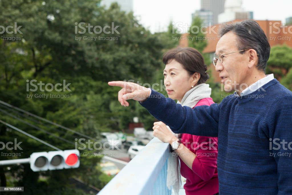 An elderly couple crossing an overpass. stock photo