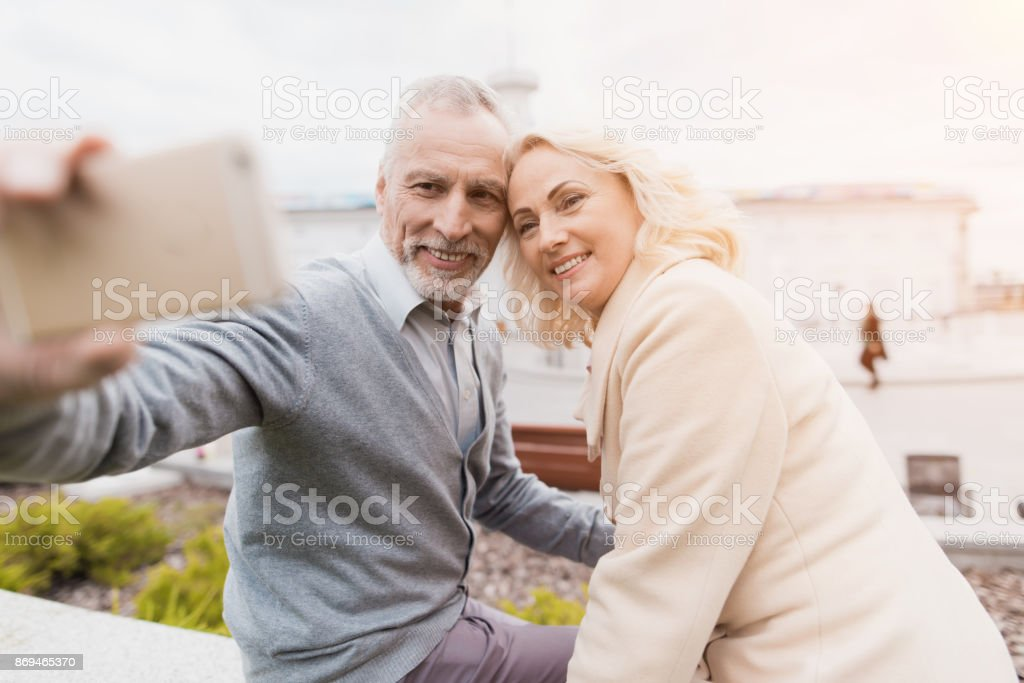 An elderly couple is sitting on the edge of a flower bed. They make selfie on smartphone стоковое фото