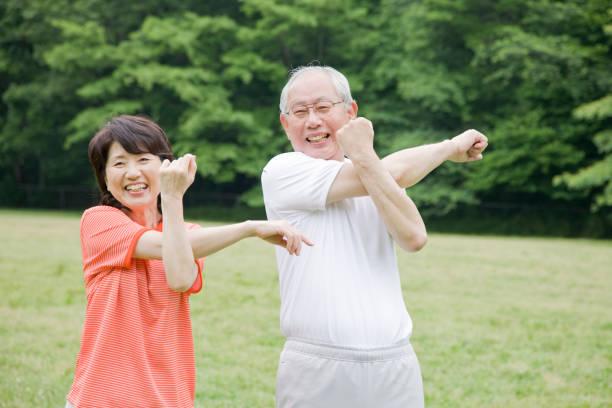 公園でラジオ体操をする老夫婦 - 体操競技 ストックフォトと画像