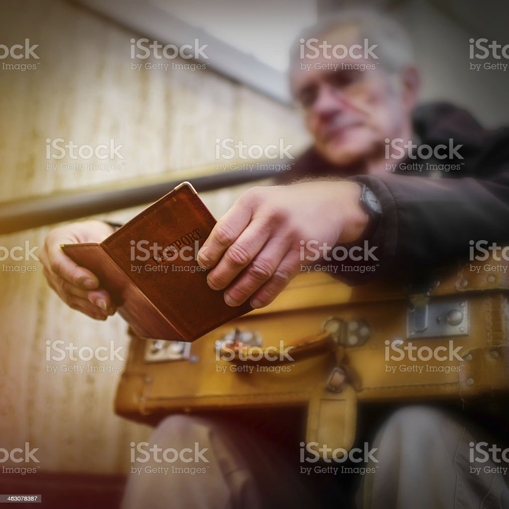 An elderly emigrant holding a yellow suitcase stock photo