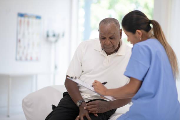 een oudere gentleman in zijn artsen kantoor ontvangen van een check-up stockfoto - prostaatkanker stockfoto's en -beelden