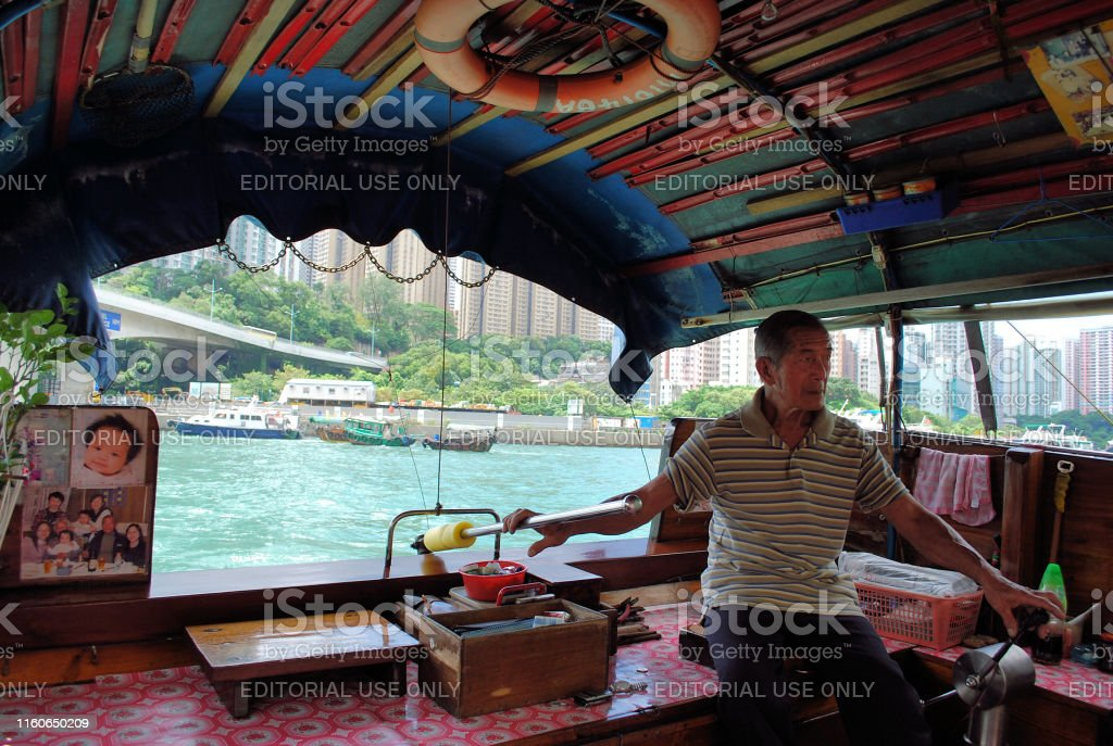 An elderly gentleman operating his Sampan tour boat in Hong Kong. The boat captain in this photograph most likely belongs to a class of traditional boat-dwelling/seafaring people called the Tankas.  The Tanka people or boat people are an ethnic subgroup predominantly associated with southern China.  Many of the Tanka people now live onshore, but some from the older generations still live on their boats. Aberdeen - Hong Kong Stock Photo