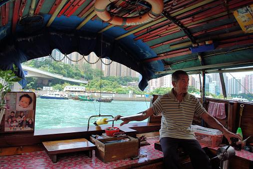 An Elderly Gentleman Operating His Sampan Tour Boat In Hong Kong Stock Photo - Download Image Now