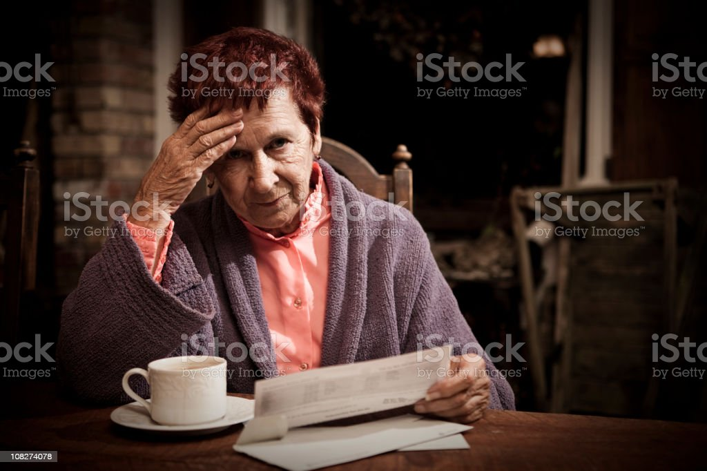 An elderly lady sat looking stressed reading bills stock photo