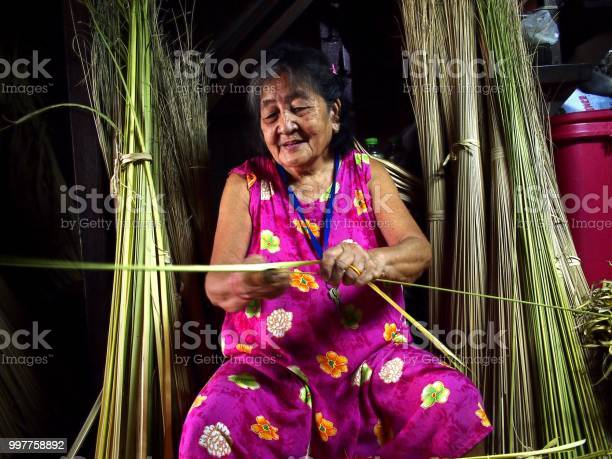 An elderly lady trims coconut tree leaves to be used as packaging for picture id997758892?b=1&k=6&m=997758892&s=612x612&h=qykfqvdjpeqxfimtm0ddthz3oti24qtgpv s3hmouxs=