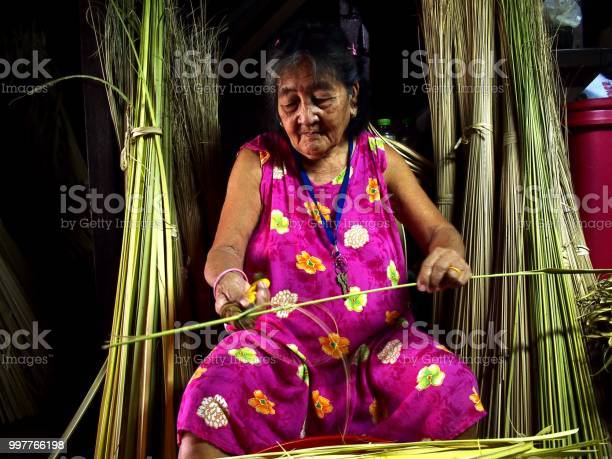An elderly lady trims coconut tree leaves to be used as packaging for picture id997766198?b=1&k=6&m=997766198&s=612x612&h=bf25sqef jrcakywscjd7ax1o81rxglfq1efhztvqs0=