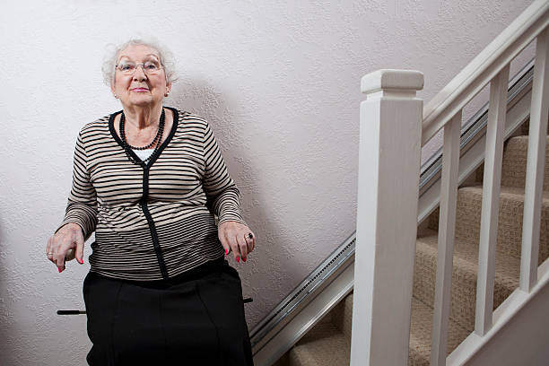 An elderly lady using a stairlift stock photo