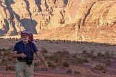 Wadi Rum Desert, Jordan 03.31.2010: An elderly male caucasian tourist  wearing traditional Jordanian keffiyeh head wrap is hiking alone in the desert. Red sandstone cliffs are seen in background