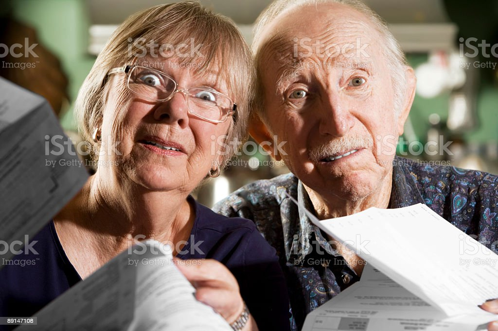 An elderly man and woman holding up their bills royalty-free stock photo