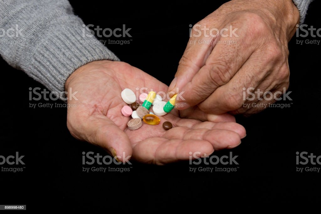 An elderly man holds a lot of colored pills in old hands. Painful old age. Health care of older people stock photo