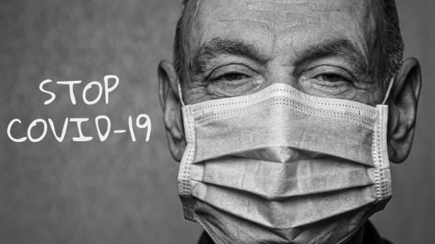 starszy mężczyzna w masce medycznej z napisem stop covid-19. grupa ryzyka. czarno-białe zdjęcie. koncepcja covid-19. choroba koronawirusowa. - covid testing zdjęcia i obrazy z banku zdjęć