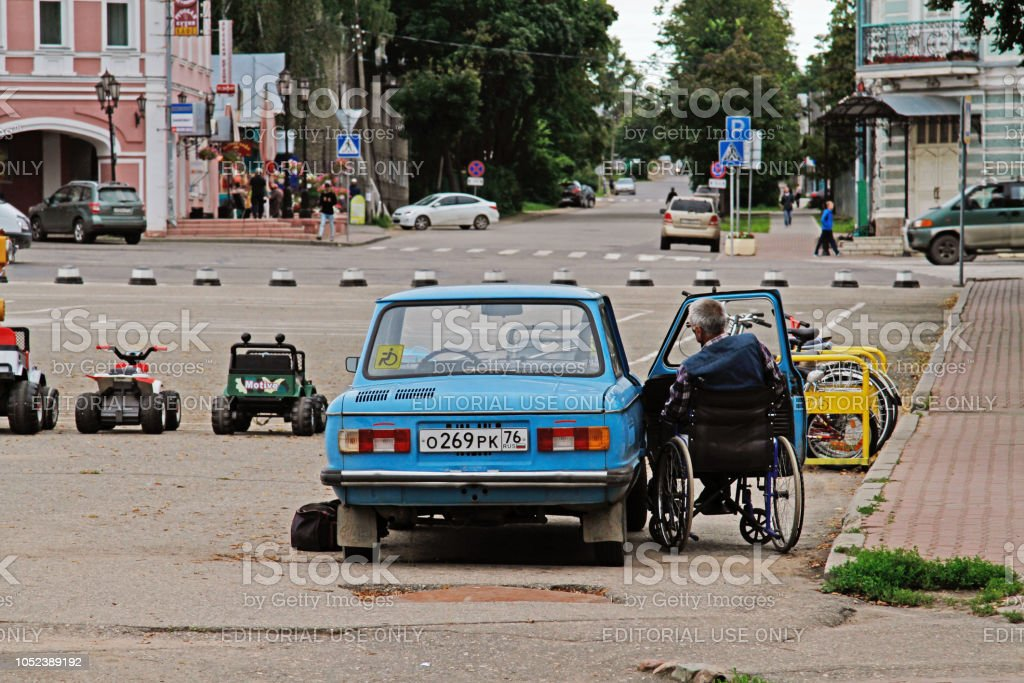 An elderly man in a wheelchair is next to the old car Zaporozhets GAZ 968 in Uglich stock photo