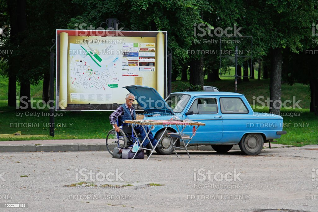 An elderly man in a wheelchair selling souvenirs on the background of an old car Zaporozhets GAZ 968 in Uglich stock photo
