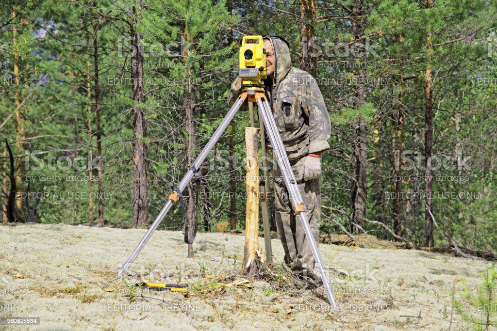 An elderly man is a surveyor at work in the overgrown taiga. Determination of coordinates stock photo