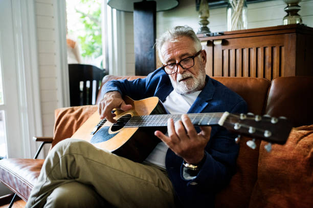 An elderly man is playing guitar An elderly man is playing guitar hobbies stock pictures, royalty-free photos & images