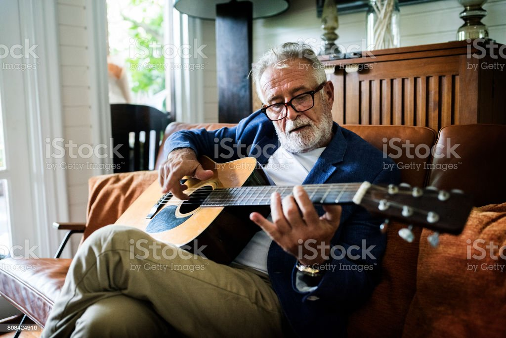 An elderly man is playing guitar stock photo