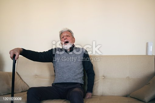 875602488 istock photo An elderly man is sitting alone at home with his walking cane and feeling a pain 1201520009