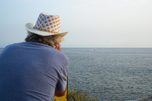 An elderly man looking through the tourist telescope turned towards infinity. Seascape of the blue Atlantic ocean. Coin-operated binoculars for landscape exploration