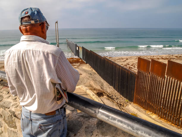 An elderly man looks at the steel wall on the US-Mexico border in Tijuana Beach Tijuana, Mexico, May 23 - A man view from the Mexican side the steel wall on the border between the United States and Mexico on the Pacific coast of Tijuana. In the background the Imperial Beach in US territory. frontier field stock pictures, royalty-free photos & images