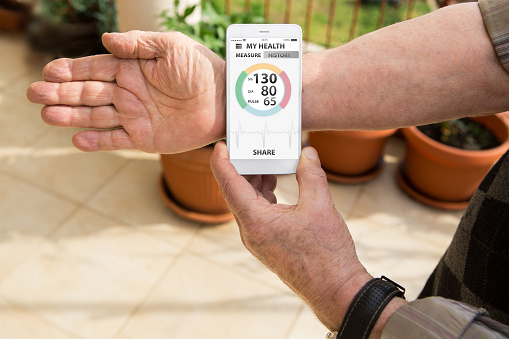 istock An elderly man measures blood pressure and pulse by mobile phone 941703000