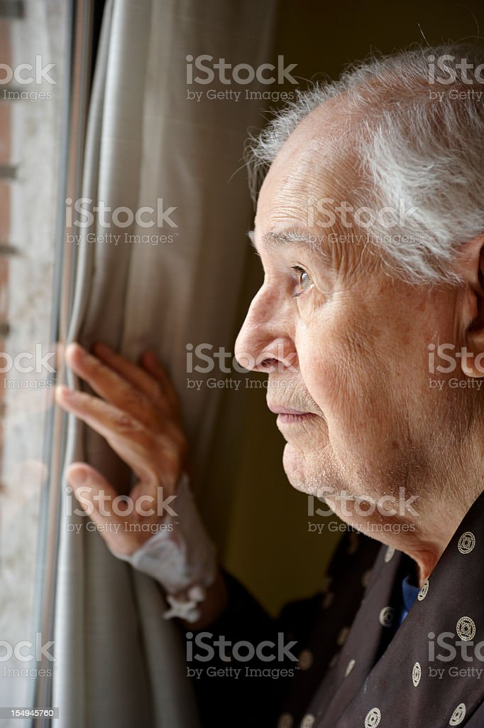An elderly man peers through a window holding curtain aside  royalty-free stock photo