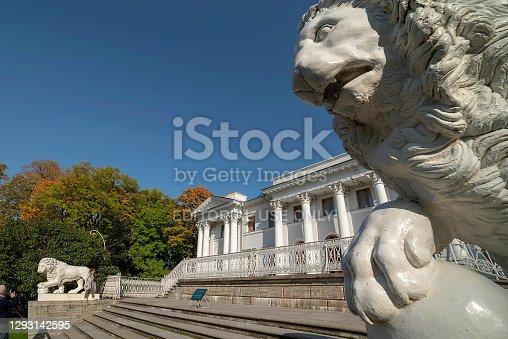 Saint-Petersburg, Russia – September 24, 2020: An elderly man photographs his granddaughter near a lion sculpture on Yelagin Island
