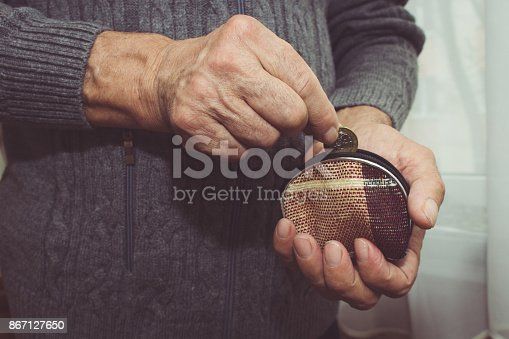 istock An elderly man puts a coin in an empty wallet. Poverty in retirement concept. Special toning 867127650