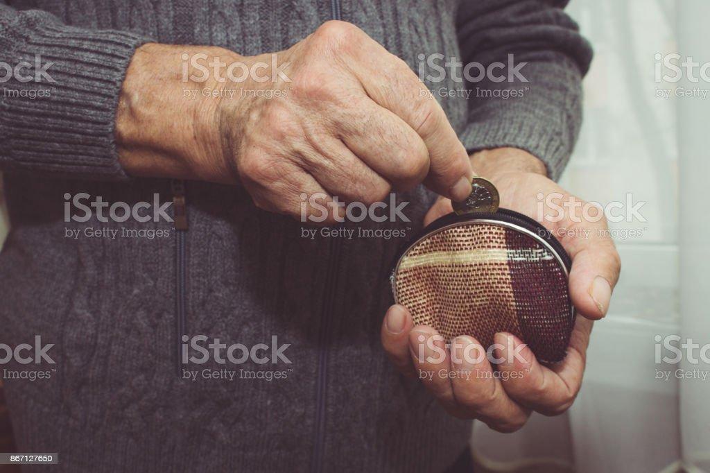 Um homem idoso coloca uma moeda em uma carteira vazia. Pobreza no conceito de aposentadoria. Tonificação especial - foto de acervo