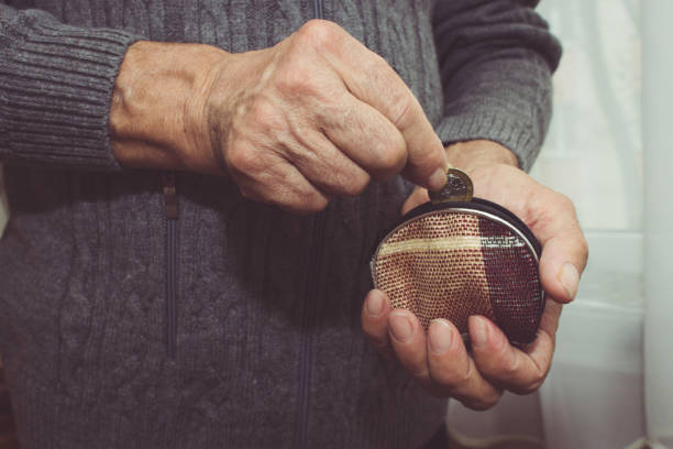 An elderly man puts a coin in an empty wallet. Poverty in retirement concept. Special toning stock photo