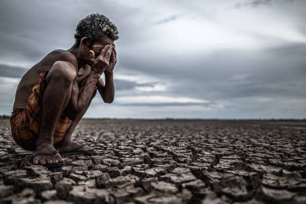 An elderly man sat bent his knees at dry ground and hands closed on his face,global warming stock photo