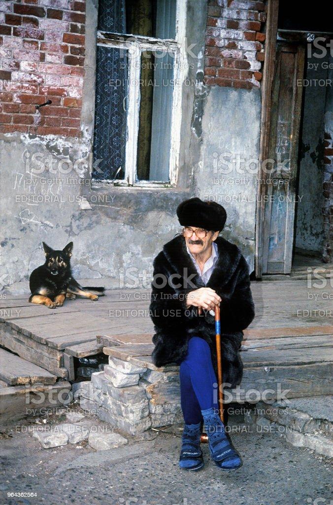 Um homem idoso senta-se no pátio da antiga casa dos tempos, do Império Russo - Foto de stock de Adulto royalty-free