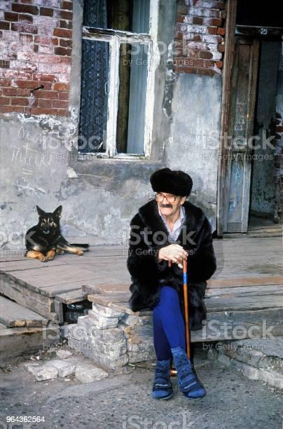 Foto de Um Homem Idoso Sentase No Pátio Da Antiga Casa Dos Tempos Do Império Russo e mais fotos de stock de Adulto