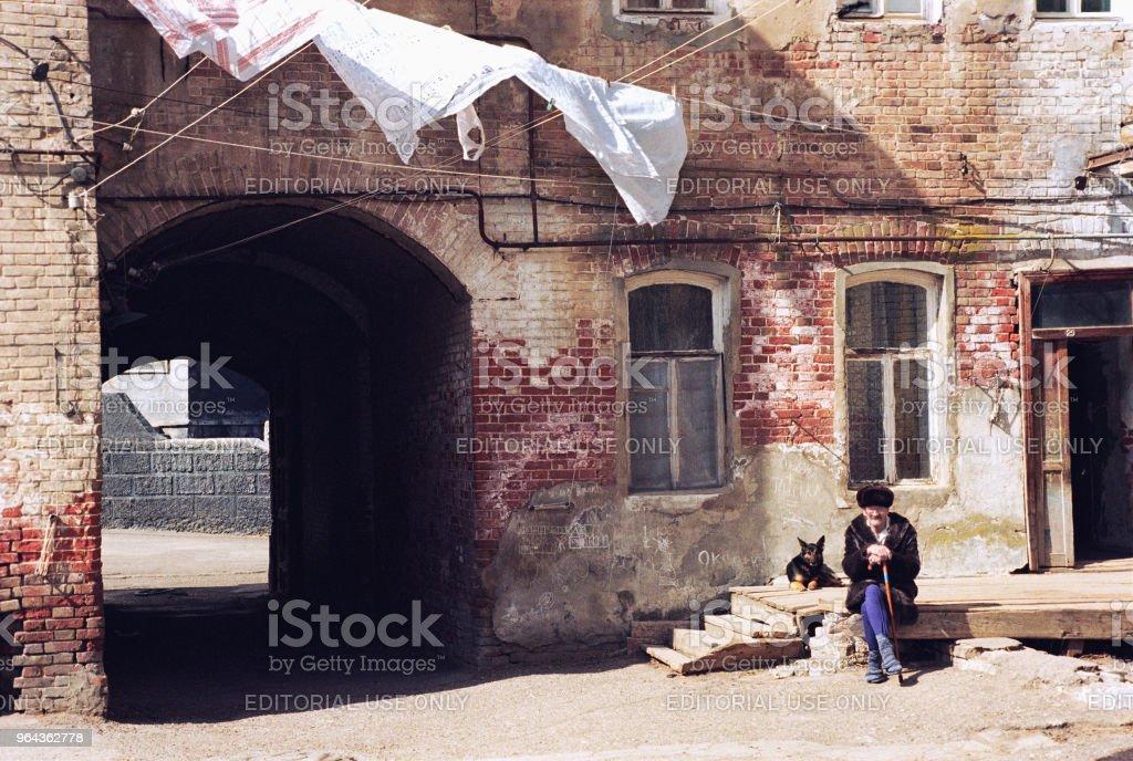 Een oudere man zit op de binnenplaats van het oude huis van de tijden, van Russische Rijk - Royalty-free 1990-1999 Stockfoto