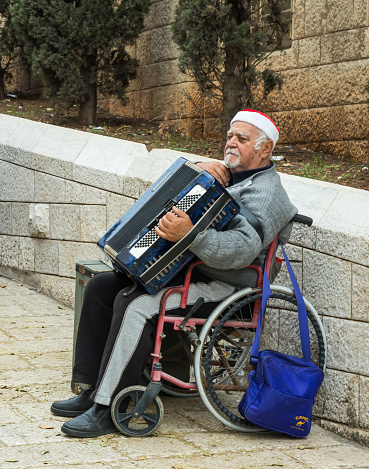 istock An elderly man sits on a wheelchair and holds an accordion in his hands in the old city of Nazareth in Israel 904186788