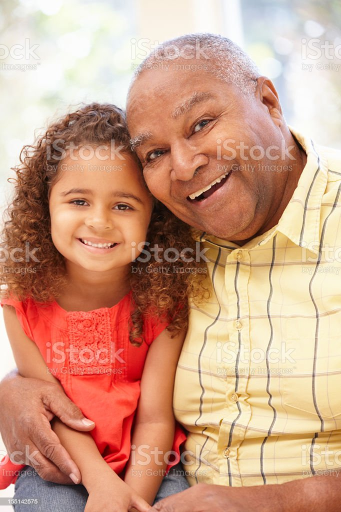 An elderly man smiling with his granddaughter on his lap royalty-free stock photo