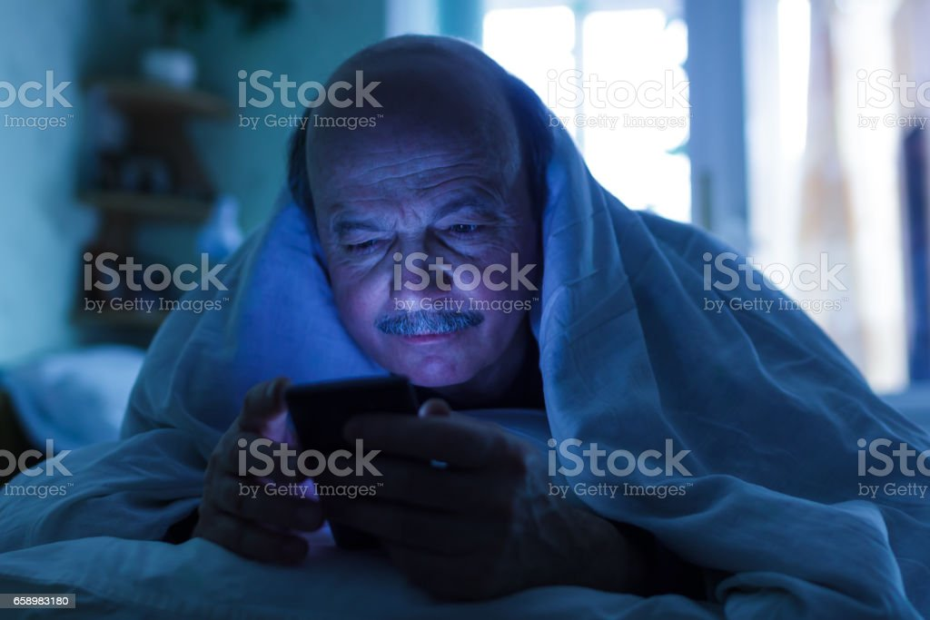 An elderly man tries to fall asleep and checks the mail or calls on the phone. Addiction on the Internet, a problem with sleep royalty-free stock photo