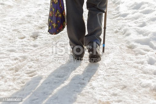 an elderly man with a stick and a shopping bag walks through the dirty, loose snow