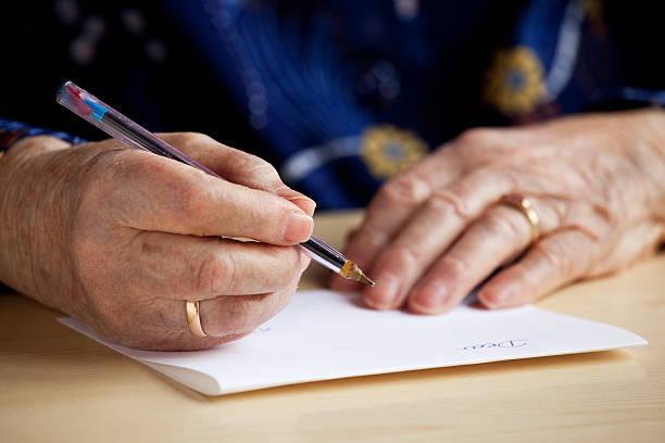 An elderly man writing a letter stock photo