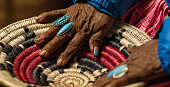 istock An Elderly Native American Woman (Navajo) Wearing Turquoise Rings on Her Fingers Touches a Woven Navajo Basket 1219298304