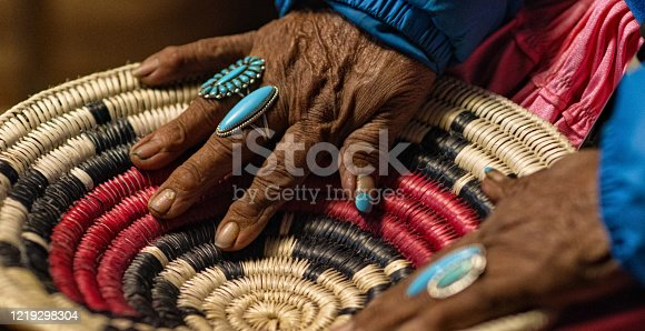 An Elderly Native American Woman (Navajo) Wearing Turquoise Rings on Her Fingers Touches a Woven Navajo Basket