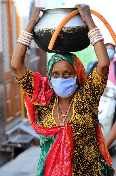 India: Water Crisis amid COVID-19 Lockdown Beawar, Rajasthan, India - May 3, 2020: An elderly rajasthani woman carry pot filled with drinking water on her head during the nationwide lockdown in wake of the novel coronavirus pandemic (COVID-19). amid stock pictures, royalty-free photos & images