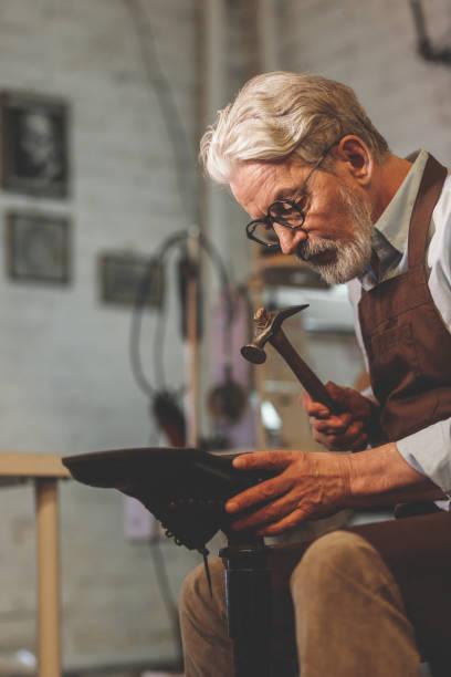 Ein älterer Schuhmacher im Atelier – Foto