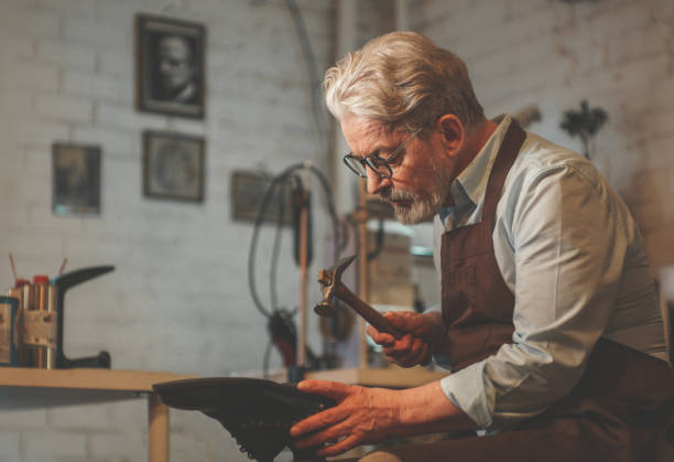 An elderly shoemaker in the workshop stock photo